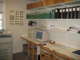 Photo of desk with shelves above holding numerous notebooks